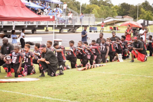Young Black men kneeling on green football field in black and red uniforms