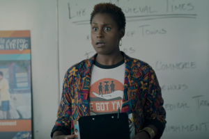 Black woman in multi-colored cardigan and white t-shirt with orange and black logo, holding black clipboard