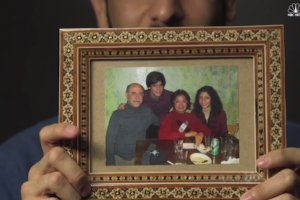 Family photograph in brown frame held by hand against grey background