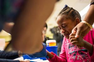 Tears stream down the face of Morgan Walker, age 5 of Flint, as she gets her finger pricked for a lead screening on January 26, 2016, at Eisenhower Elementary School in Flint, Michigan.