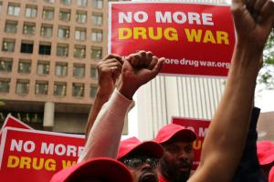 "People wearing red caps hold power fists and signs that say ""No More Drug War."""