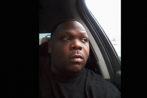 Michael Sabbie sits in a car, looks away from the camera