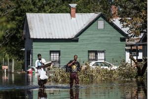 Vance Barden, right, and Wayne Edwards carry personal items through a flooded street caused by remnants of Hurricane Matthew on October 11, 2016, in Fair Bluff, North Carolina. Thousands of homes have been damaged in North Carolina.