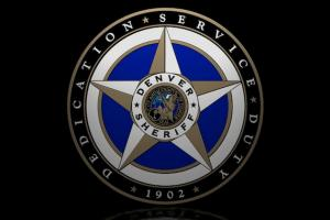Blue and gold police seal with white text against black background