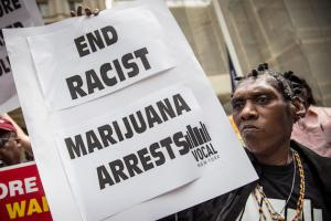 "Black woman wearing plaits holds up a sign that says, ""End racist weed arrests."""
