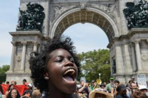 A young Black woman in a black t-shirt chants during a Eric Garner march
