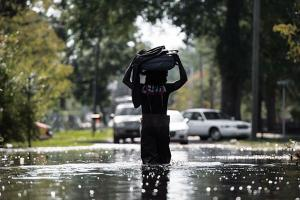 A man carries personal items through a flooded street caused by remnants of Hurricane Matthew on October 11, 2016, in Fair Bluff, North Carolina. The severity of the storm was felt throughout the state with flooding just as bad in Princeville, N.C.