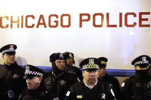 Police in black patrol attire with black-and-white checkered banners on hats against white police truck with red text