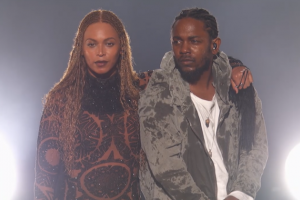 Black woman in black patterned one-piece suit next to Black man in light green sweatshirt and white t-shirt against white-lit grey background