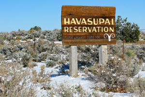 "Brown sign with yellow text reading ""Havasupai Reservation"" on two light brown poles against white snow-covered desert"