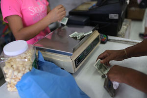 Brown hands exchange green dollar bills with Brown person in pink shirt behind grey counter with grey-brown scale, black cash register and clear container of off-white garlic cloves