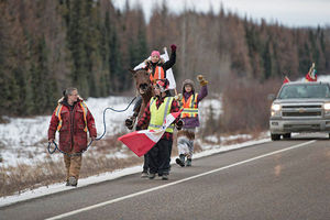 Tina Johnson walks alongside Charlleen Charles, on horseback, and Ricky Mckenzie and Celine Desiree Jade Charles, with her fist raised as they make their way to Standing Rock, North Dakota, from Saskatchewan, Canada.
