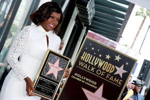 Black woman in white dress holding brown plaque with gold border and gold text and red-pink star against brown podium with gold text and red star with black, brown and white storefronts in background