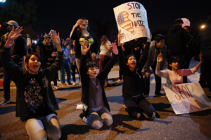 Protesters kneel with their hands up.
