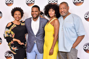 Black woman in black shirt next to Black man in blue suit next to Black woman in yellow dress next to Black man in light blue shirt against white background with black, brown and white logos