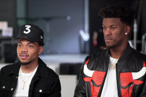 Black man wearing black baseball cap and black denim jacket with white t-shirt seated next to Black man in red, black and white leather jacket with white t-shirt in front of blurry studio background