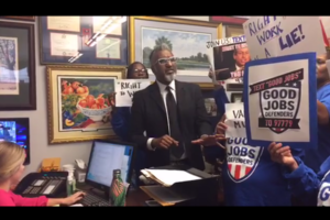 Man in suit surrounded by protestors in office