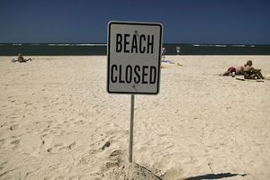 "Sign on beach reads, ""Beach closed."""