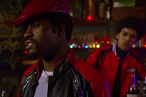 Black man in black-and-red leather jacket and red cap and white t-shirt in front of Black man in red-and-black leather jacket with black t-shit against red, yellow, blue and green-lit brown bar