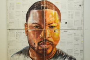 Black artist's self portrait on white pieces of paper with black ink, mounted onto white wall