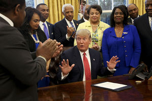 Black men and women in black suits, yellow blazer and blue dresses stand around White man in navy suit seated at brown desk in room with yellow wall