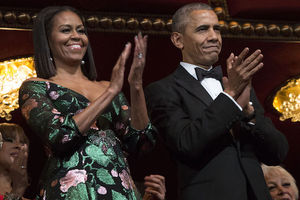 Black woman in green, pink and black dress stands clapping next to Black man in black-and-white tuxedo in theater balcony with maroon and gold ceiling