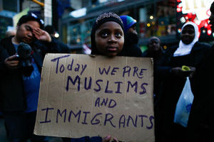 """Brown girl in hijab holds sign that reads, """"Today we are Muslims and immigrants."""""""
