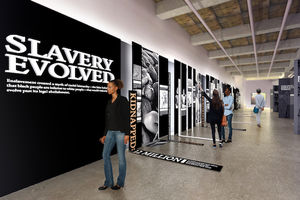 Museum room with grey walls, brown ceilings and exhibits in greyscale and black with white text, with Black people walking on grey floor