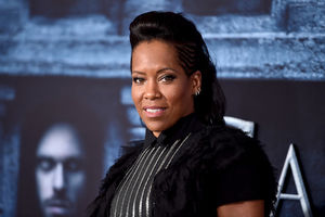 Black woman in black outfit with silver striped embroidery in front of blue-and-black background