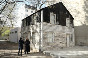 Black woman in brown coat and black sunglasses speaks to White woman in navy jacket and black pants while standing in front of grey and brown wooden house in neighborhood with green trees and grey buildings