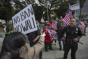 "A woman in a taupe coat stands before a uniformed police officer holding up a sign that says ""No ban, no wall."""