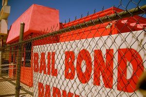 "Sign reads ""Bail Bonds"" behind chain-link fence"