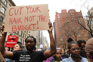 """Protestors, one holds sign that reads, """"Cut your hair, not the budget."""""""