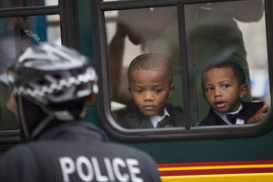 Balck boys through bus window, police officer outside bus.