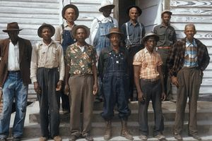 Black men in multicolored clothing assembled on brown stone steps in front of white building