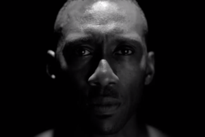 Black-and-white image of a Black man in front of a Black background