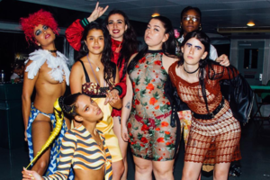 Black and brown women and gender-non-conforming individuals in multicolored clothing standing in a group in front of a grey and black wall