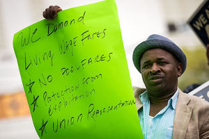 """Black man holds sign that reads: """"We demand living wage fares, no pool fare, protection from exploitation, union representation."""""""