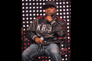 Black man sits in black baseball cap and jacket with grey lettering and dark blue jeans on black chair in front of purple background