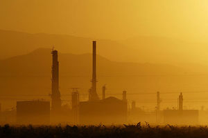 The sun rises over the Kern Oil and Refining Co. refinery on August 12, 2004 near the town of Lamont, southeast of Bakersfield, California.
