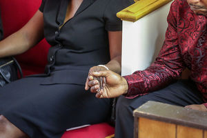 Black woman and man hold hands in church.