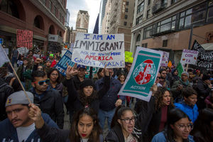 """Crowd of protestors, one holds sign that says, """"I am an immigrant. Ask me how to make America great again."""""""