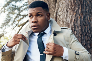 Black man in white dress shirt and navy tie and pants and tan overcoat in front of brown trees with green leaves