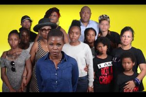Black woman in blue denim shirt surrounded by Black women, children and man in multi-colored clothing in front of yellow screen
