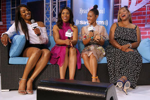 Black woman in white shirt and black shorts sits next to Black woman in pink dress next to Black woman in light pink patterned dress next to black woman in black dress with white dots on black couch with blue cushions in front of red-and-blue background