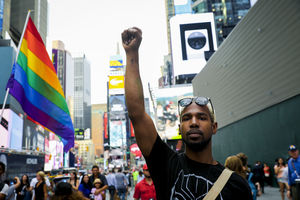 A Black man raises a fist while standing in front of a rainbow flag in Times Square