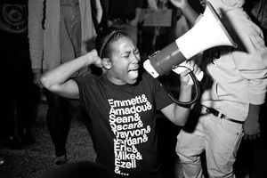 Black-and-white image of Black woman in black t-shirt with white text holding white megaphone in front of Black people in black and white and grey clothing