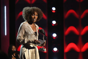 Black woman in gold dress stands behind black microphone and in front of red and black background while holding golden statue