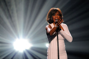 Black woman in White dress stands behind black microphone in front of white light on black background