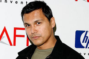 Native man in green shirt and black jacket in front of white wall with red and navy and black insignia